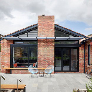 Photo of a transitional one-storey brick red house exterior in Melbourne with a gable roof and a tile roof.