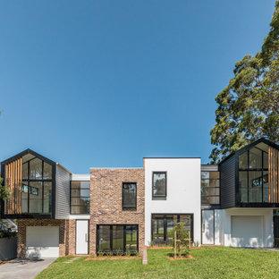 Cette photo montre une façade de maison double moderne de taille moyenne et à un étage.