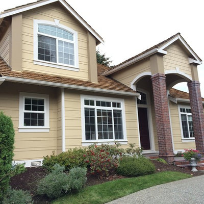 Mid-sized traditional beige two-story vinyl exterior home idea in Seattle with a hip roof