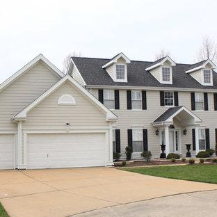 Réalisation d'une grand façade de maison beige tradition à un étage avec un revêtement en panneau de béton fibré, un toit à deux pans et un toit en shingle.