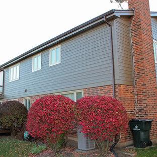 Imagen de fachada de casa marrón, clásica, pequeña, a niveles, con revestimiento de aglomerado de cemento