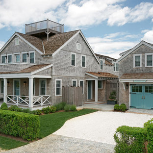 Ejemplo de fachada marrón, costera, de dos plantas, con revestimiento de madera y tejado a dos aguas