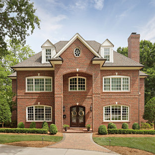 Mid-sized traditional red three-story brick exterior home idea in Other with a shingle roof