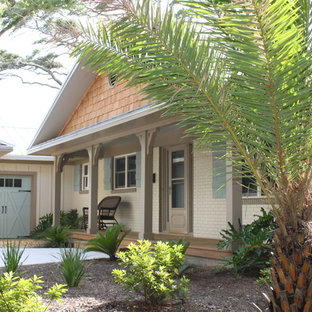 Mid-sized tropical beige one-story brick exterior home idea in Jacksonville with a metal roof