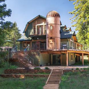 Modelo de fachada verde, de estilo de casa de campo, grande, de tres plantas, con revestimiento de madera