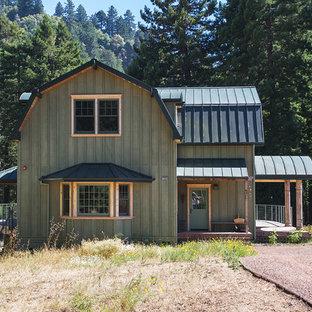 Foto de fachada verde, campestre, de dos plantas, con revestimiento de madera y tejado a doble faldón