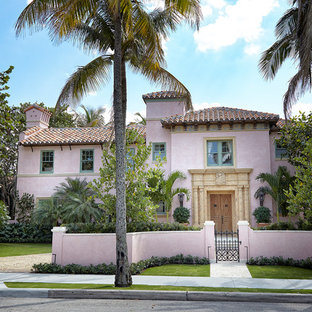 Tuscan pink two-story house exterior photo in Miami with a hip roof and a tile roof