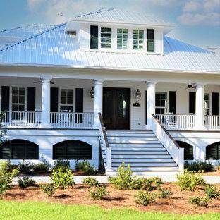 Foto de fachada de casa costera con revestimiento de madera, tejado a cuatro aguas y tejado de metal