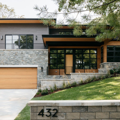 Contemporary two-story mixed siding house exterior idea in Chicago with a hip roof