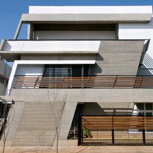 Foto della facciata di una casa ampia bianca contemporanea a tre piani con rivestimento in cemento