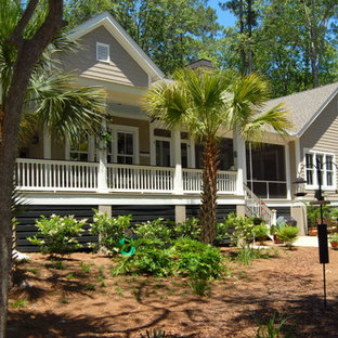 Example of a mid-sized island style beige two-story mixed siding exterior home design in Atlanta with a shingle roof