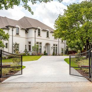 Стильный дизайн: огромный, двухэтажный, кирпичный, белый частный загородный дом с крышей из гибкой черепицы и вальмовой крышей - последний тренд