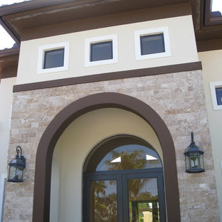 Inspiration for a large mediterranean beige one-story stucco house exterior remodel in Miami with a hip roof and a tile roof