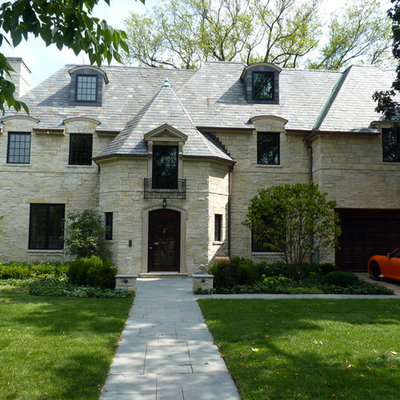 Example of a large classic three-story stone exterior home design in Chicago