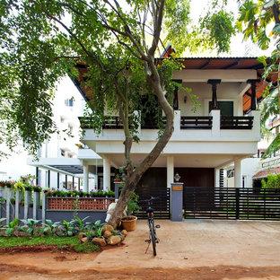 Свежая идея для дизайна: двухэтажный, белый частный загородный дом в восточном стиле с вальмовой крышей и черепичной крышей - отличное фото интерьера