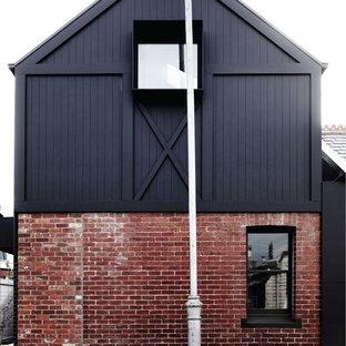 Ispirazione per la facciata di una casa nera contemporanea a due piani di medie dimensioni con rivestimenti misti e tetto a capanna