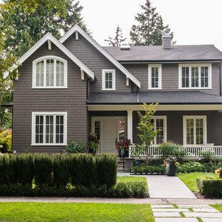 Ejemplo de fachada de casa marrón, clásica, de tamaño medio, de dos plantas, con revestimiento de madera, tejado a dos aguas y tejado de teja de barro