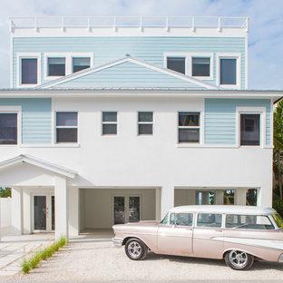 Ejemplo de fachada de casa azul, costera, grande, de tres plantas, con revestimiento de hormigón, tejado plano y tejado de metal