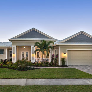Mid-sized tropical green one-story mixed siding exterior home idea in Miami with a metal roof