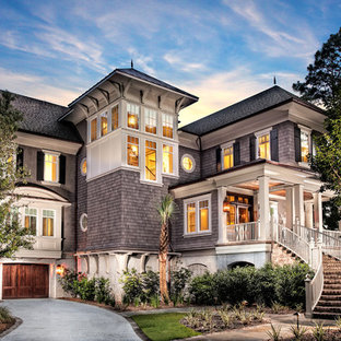 Design ideas for a large beach style grey exterior in Charleston with three or more storeys, wood siding and a gable roof.