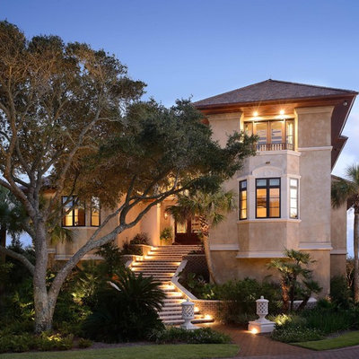 Large tuscan beige two-story stucco gable roof photo in Charleston