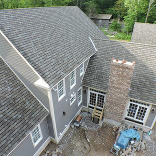 Idee per la facciata di una casa unifamiliare ampia grigia classica a tre o più piani con rivestimento con lastre in cemento, tetto a capanna e copertura mista