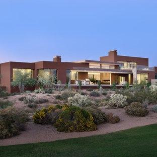 На фото: большой, двухэтажный, розовый частный загородный дом в современном стиле с облицовкой из цементной штукатурки, плоской крышей и зеленой крышей с