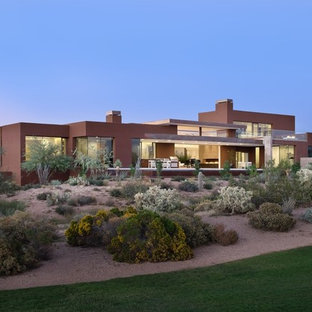 Inspiration for a large contemporary pink two-story stucco exterior home remodel in Phoenix with a green roof