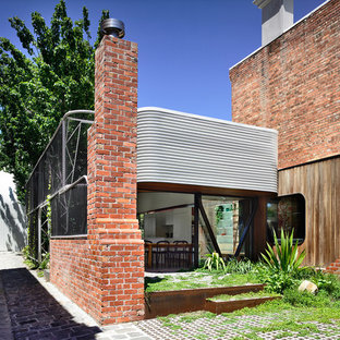 Inspiration for a victorian two-story glass exterior home remodel in Melbourne with a metal roof