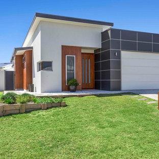 Réalisation d'une façade de maison multicolore design de taille moyenne et de plain-pied avec un revêtement en panneau de béton fibré et un toit plat.