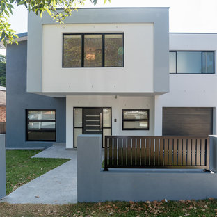 Inspiration for a contemporary two-storey stucco exterior in Sydney with a flat roof.