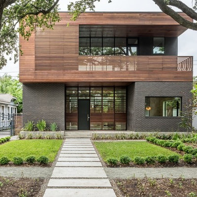 Inspiration for a large contemporary black two-story mixed siding flat roof remodel in Houston