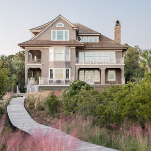 Example of a coastal three-story wood exterior home design in Charleston with a shingle roof