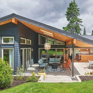 Идея дизайна: одноэтажный, серый частный загородный дом среднего размера в стиле ретро с двускатной крышей и металлической крышей
