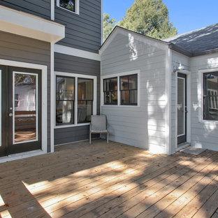 Modelo de fachada gris, clásica renovada, pequeña, de dos plantas, con revestimiento de aglomerado de cemento y tejado a dos aguas