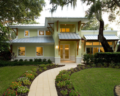Example Of An Island Style Yellow Two Story Exterior Home Design In Tampa