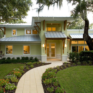 Example of an island style yellow two-story exterior home design in Tampa