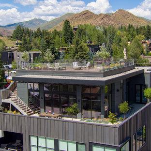 Immagine della facciata di un appartamento grande grigio classico a due piani con rivestimento in metallo, tetto piano e copertura mista