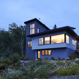 This is an example of a beach style house exterior in Minneapolis with three or more storeys, metal siding, a shed roof and a metal roof.