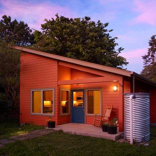 Стильный дизайн: одноэтажный, оранжевый мини-дом в современном стиле с односкатной крышей - последний тренд