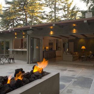 На фото: одноэтажный, большой, серый дом в современном стиле с облицовкой из цементной штукатурки и плоской крышей с