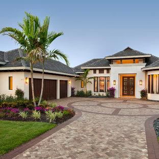 Inspiration pour une façade de maison beige ethnique de plain-pied avec un toit à quatre pans.