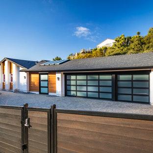 На фото: большой, одноэтажный, разноцветный частный загородный дом в современном стиле с комбинированной облицовкой, крышей из гибкой черепицы и серой крышей