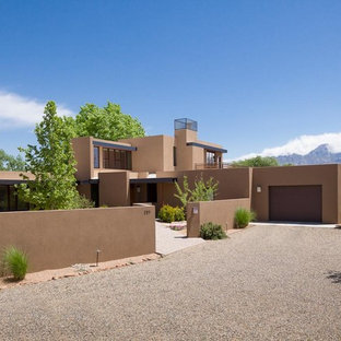 Inspiration for a large southwestern beige two-story stucco exterior home remodel in Albuquerque with a metal roof