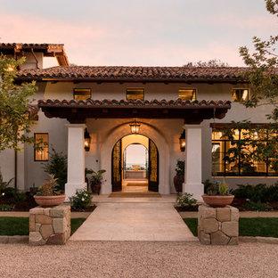 На фото: двухэтажный, белый частный загородный дом в средиземноморском стиле с облицовкой из цементной штукатурки, двускатной крышей и черепичной крышей с