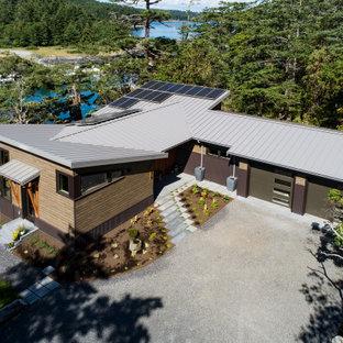 Пример оригинального дизайна: одноэтажный, разноцветный частный загородный дом среднего размера в стиле ретро с комбинированной облицовкой, крышей-бабочкой и металлической крышей