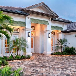 Foto della facciata di una casa bianca tropicale a un piano con rivestimento in stucco e tetto a padiglione