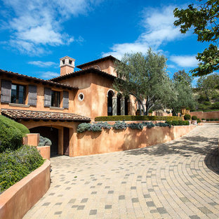 Large transitional orange three-story stucco house exterior idea in Orange County with a tile roof