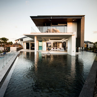 Huge tropical white two-story glass exterior home idea in Gold Coast - Tweed with a hip roof