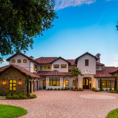 Example of a large tuscan white two-story stone exterior home design in Austin with a tile roof